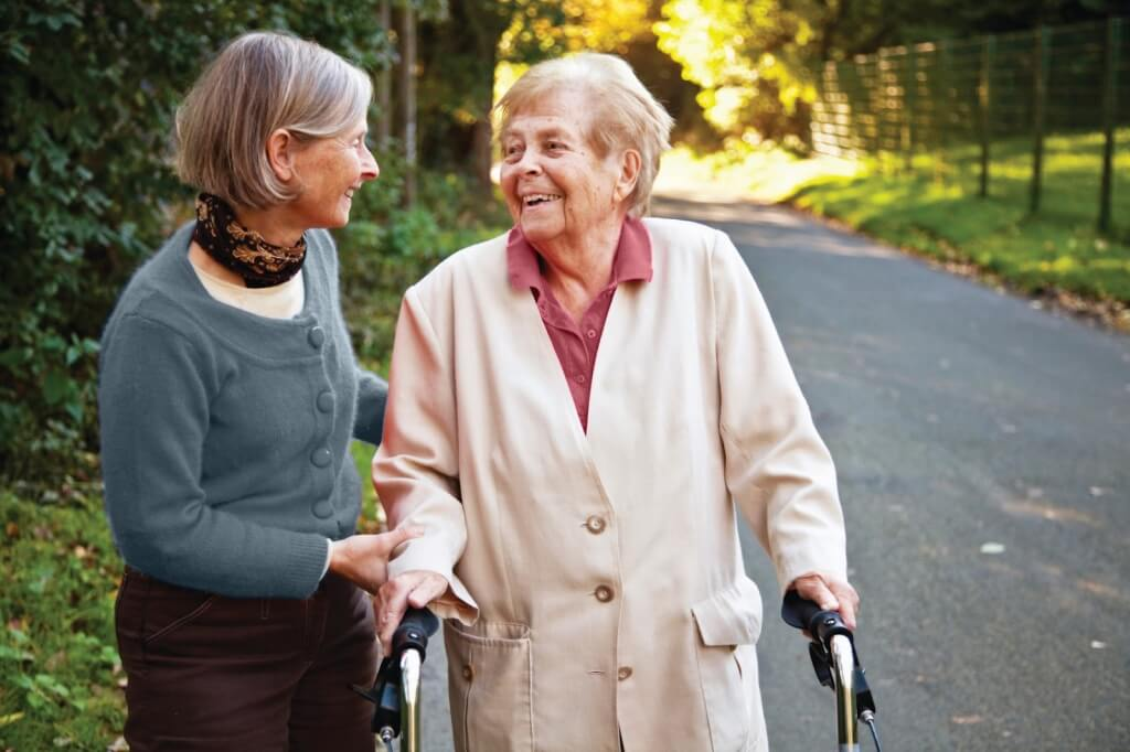 Senior woman accompanying an elderly lady with a walker in a park