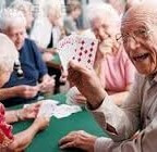 Group of seniors playing cards around a table