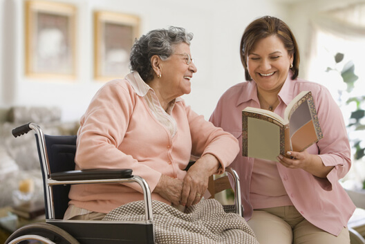 Older woman reading to an elderly lady in a wheelchair