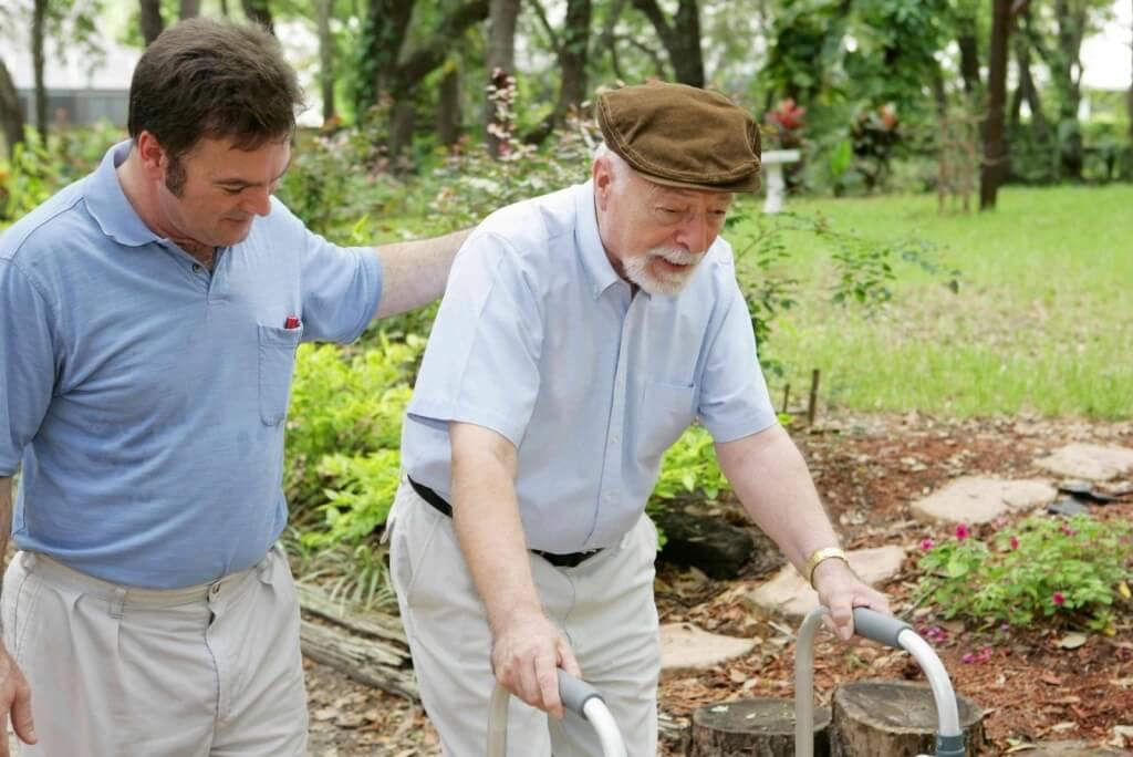 Senior man caring for an elderly man with a walker in a garden